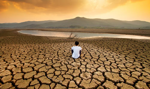 A man sat looking at a small amount of water in an almost dry reservoir